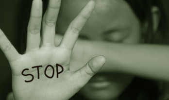 niña tapandose los ojos y con la palabra stop escrita en su otra mano