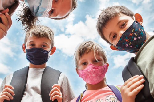 Low angle view of Children wearing protective face masks and backpacks. They are in circle looking at the camera. Cloudy blue sky behind. Concept Back to school after coronavirus.